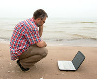 Elderly businessman sitting with notebook on beach Stock Photography