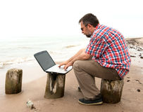 Elderly businessman sitting with notebook on beach Stock Photo