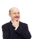Elderly businessman smiling rubbing his chin Stock Photo
