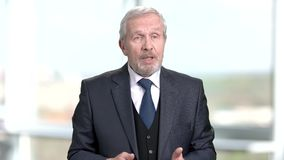 Elderly businessman talking on blurred background. Senior executive reported at seminar. Speech of company leader stock video