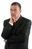 Elderly businessman is thinking about something isolated on whit Stock Image