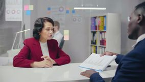 Elderly businesswoman and her Afro American partners. Elderly businesswoman and her Afro American partner discussing details of their contract. Business and stock video footage