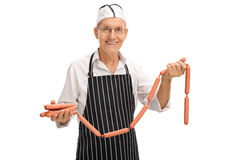 Elderly butcher holding sausages Stock Photo