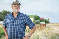 Elderly captain on the sea shore Royalty Free Stock Image