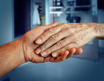 Elderly Care. And senior health services with the hand of a young person holding and helping an old and aging retired patient needing in home medical help due stock photo