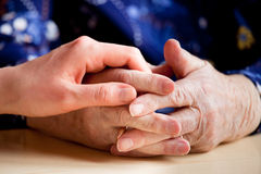 Elderly Care. A young hand holding an elderly pair of hands royalty free stock photos