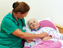 Elderly care. Caregiver with an elderly patient at home royalty free stock photo