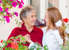 Elderly care. Happy elderly women and her helpful assistant Royalty Free Stock Images