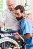 Elderly care nurse helping senior from bed to wheel chair. In hospital or nursing home royalty free stock images
