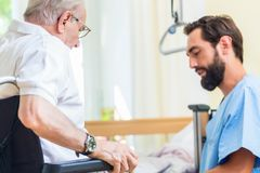 Elderly care nurse helping senior from bed to wheel chair Royalty Free Stock Photography