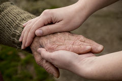 Elderly care. Old and young person holding hands. Elderly care and respect royalty free stock photo