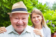 Elderly care outdoor. Smiling elderly men with beautiful young granddaughter posing in the park royalty free stock photo