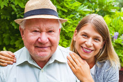 Elderly care outdoor. Smiling elderly men with beautiful young granddaughter posing in the park stock image