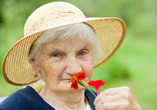 Elderly care. Picture of an elderly woman holding a red flower Stock Images