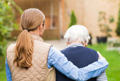 Elderly care. Young carer walking with the elderly women in the park stock photos