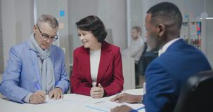 Elderly caucasian couple setting up a contract. With afro american lawyer, man signing papers in modern office stock video footage