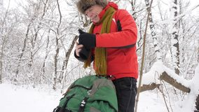 Elderly Caucasian man removes winter gloves and throws them on the floor in a snow-covered forest. Thick dense thicket. Of trees and roots in in the snow stock footage
