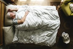 Elderly Caucasian man sleeping on the bed stock image