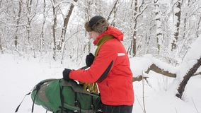 Elderly Caucasian man takes off his backpack and puts it on the floor. Thick dense thicket of trees and roots in in the. Snow-covered forest. Hike and halt stock footage