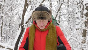 Elderly Caucasian smiling man with Hiking Sticks walks through a snowy forest. Portrait video shooting. Thick dense. Thicket of trees and roots in in the snow stock footage