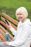 Elderly cheerful woman using smartphone while sitting on bench with sport bottle. Of water royalty free stock photo