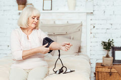 Elderly cheerless woman measuring blood pressute. Check it out. Pleasant elderly moody woamn sitting in bed and measuring blood pressure Stock Photography