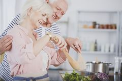 Chef teaching cooking senior woman. An elderly chef teaching cooking to a senior woman, preparing a healthy salad together Royalty Free Stock Photo