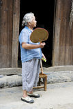 Elderly Chinese Lady at Daxu. Image of an elderly Chinese lady with fan and cucumber in hand at Daxu Ancient Town, Guilin, China Royalty Free Stock Images