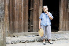 Elderly Chinese Lady Eating Cucumber. Image of an elderly Chinese lady eating cucumber at Daxu Ancient Town, Guilin, China Royalty Free Stock Photography