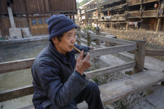 Elderly chinese man holds in his hand bamboo pipe smoking. Stock Photos
