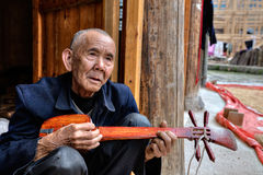 An elderly Chinese man holds local music stringed instrument, Ch Royalty Free Stock Image