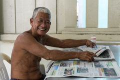 Elderly Chinese man reads newspapers at local coffeeshop Royalty Free Stock Photography