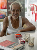 Elderly Chinese man sits at local coffeeshop Stock Image
