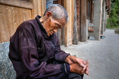 An elderly Chinese man sleeps sitting under the open sky on a ru. Zhaoxing Dong Village, Guizhou Province, China -  April 9, 2010: Aged Chinese man is sleeping Stock Images