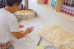 Elderly Chinese woman preparing baozi. 08/13/2016 WuYuan,China - Elderly Chinese woman is standing in a shop preparing baozi in front of a huge pile of dough Stock Photography
