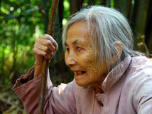Elderly chinese woman with a staff in her hand royalty free stock photos