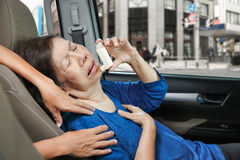 Elderly choking and holding an asthma spray. Elderly woman choking and holding an asthma spray inside car on Stock Image