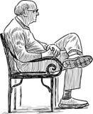 Elderly city dweller sits on the park bench Stock Photos