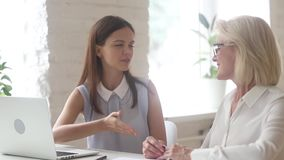Elderly client young executive manager after reached agreement shaking hands. Women business partners reached agreement shake hands sitting at desk in office stock video