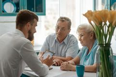 Elderly clients consulting an advisor. Positive emotions and friendly attitude. Good service, retirement and financial planning royalty free stock image