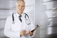 Free Elderly Confident Doctor Standing Straight And Using Clipboard In Clinic. Perfect Medical Service. Medicine And Stock Image - 183891691