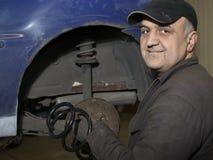 Elderly content mechanic fixing old car. Elderly mechanic fixing old blue car stock photo