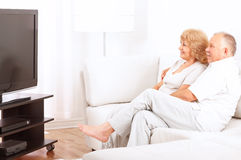 Elderly couple. Happy smiling elderly couple watching TV at home royalty free stock images