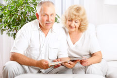Elderly couple. Happy smiling elderly couple reading a magazine at home royalty free stock photography