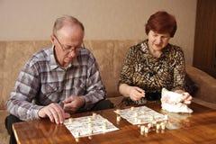 An elderly couple. Sit and play bingo Stock Photo