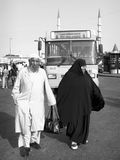 Elderly couple. An Elderly Muslim couple in traditional black and white costumes looks for their bus stop at Eminonu square on June10, 2010  in Istanbul Royalty Free Stock Photography