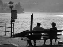 An elderly couple. Sits on the bench near the shore of the lake royalty free stock photo