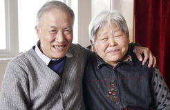 Elderly couple. Happy Chinese elderly couple at home. (Focus on his wife royalty free stock image