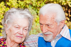 Elderly couple. Portrait of an elderly couple sitting outdoors Stock Photo