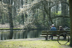 Elderly couple. On a bench near water in nature stock photos